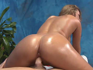 Fucking on the massage table with a brunette babe smeared in oil