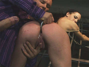 Extreme sex fucking a horny brunette tied to a fence with a hook tucked in the ass