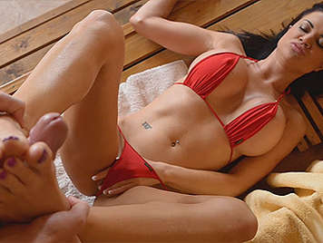 Brunette in bikini jerking with feet in a sauna