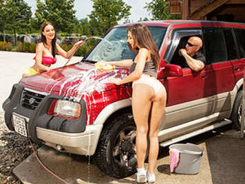 Two beautiful girls do anal threesome in the car wash