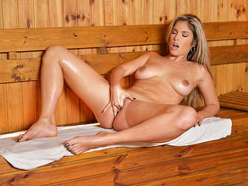 Busty blonde masturbating in a sauna gets a wet orgasm